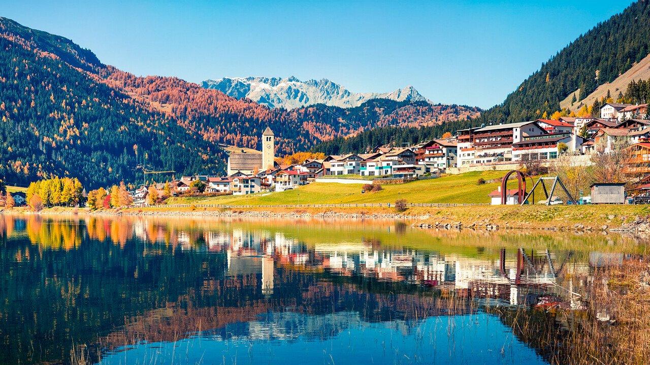 Paese di Resia riflesso nel lago in autunno