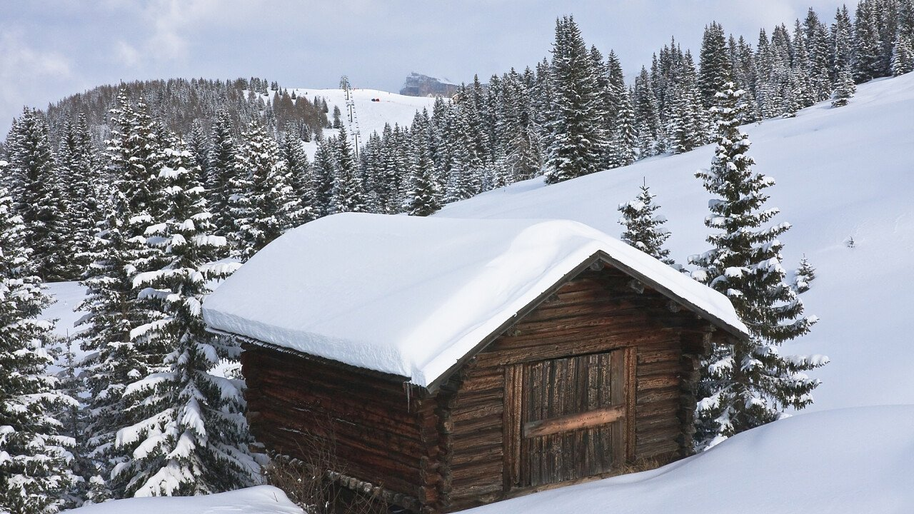 Wooden house surrounded by snow in Selva Val Gardena