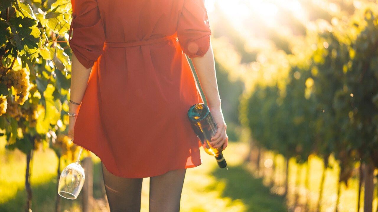 donna_vestito_rosso_tra_vigne_con_bicchiere_bottiglia_picjumbo_viktor_hanacek