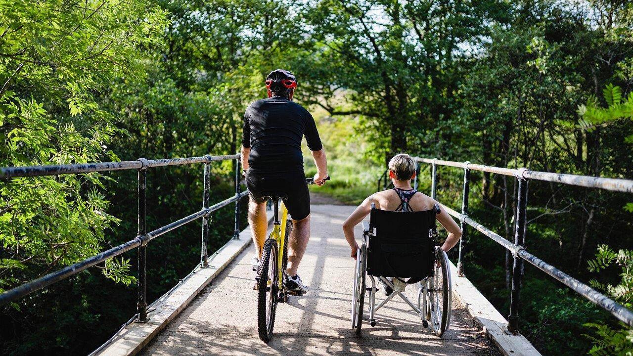 Persona in bici con affianco una persona in carrozzina