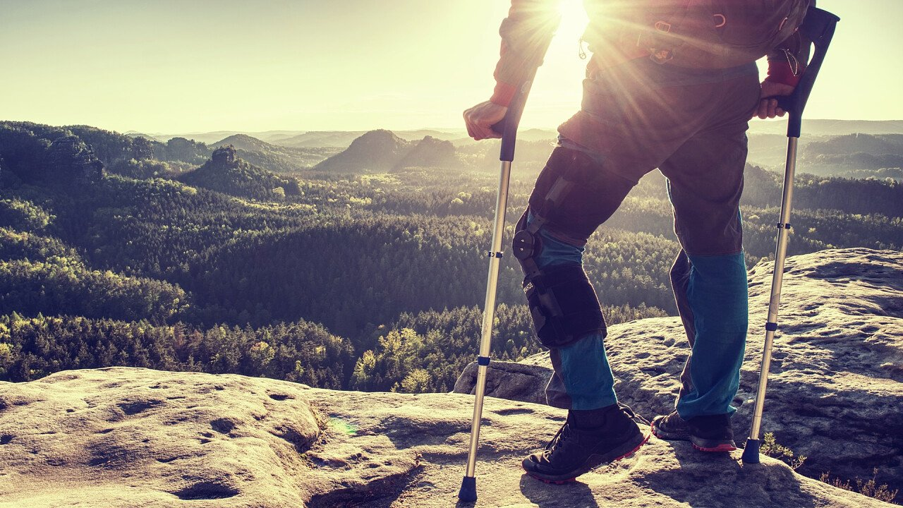 Uomo con le stampelle in montagna in inverno
