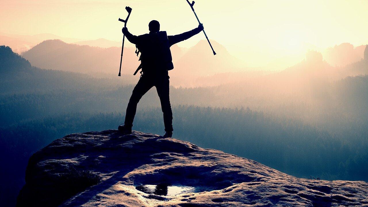 Persona con le stampelle in cima alla montagna
