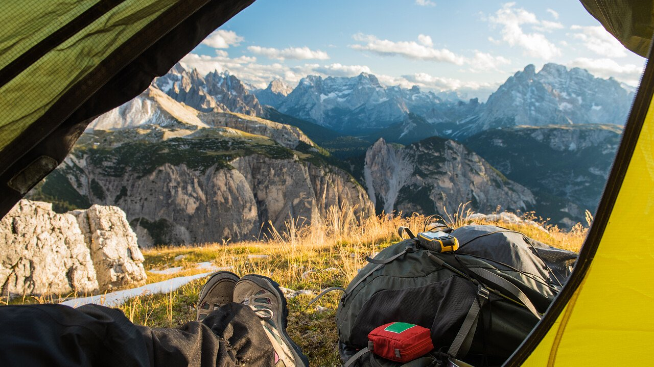 Tent with trekking backpack in the Dolomites