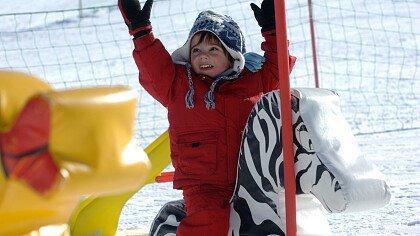 Bimbo al parco giochi sulla neve