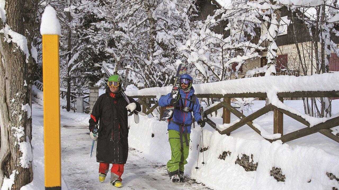 Sciatori con gli sci in spalle in Alpe Cimbra